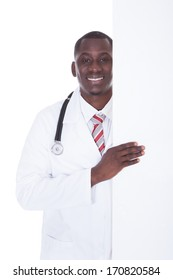 Young Male African Doctor Holding Placard Over White Background
