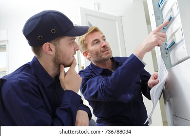 young male apprentice electrician listening to mentor