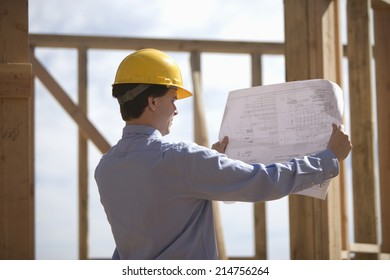 Young male architect analyzing blueprint at construction site