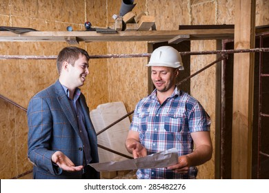 Young Male Architect and Construction Worker Foreman Inspecting Building Plans Together Inside Unfinished Building