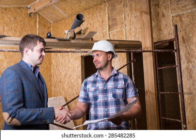 Young Male Architect and Construction Worker Foreman with Building Plans Shaking Hands Inside Unfinished House with Exposed Particle Plywood Boards