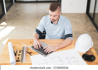 Young male architect at his workspace. Architect concept, Architects working with blueprints in the office. young intelligent architect man typing laptop search information for his project.