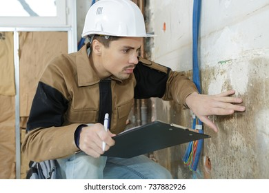 young male architect inspecting wall at construction site