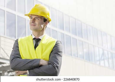 Young male architect standing arms crossed outside office building