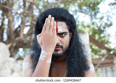 A young male artist as Ravana closes one eye during the Lord of lanka post photoshoot on December 23rd 2018 at Sai Baba temple in Bengaluru,India