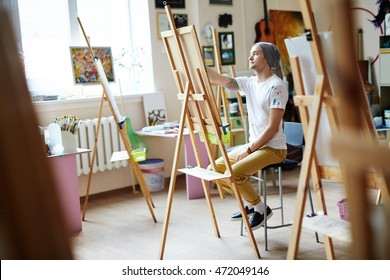 Young male artist in white shirt stained with paint sketching on easel in bright art studio with colorful painting in background.