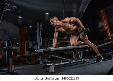 Young male athlete bodybuilder posing and doing sports exercises in the gym