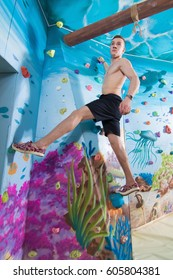 Young male athlete climber performs exercises on a climbing wall