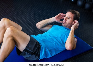 Young male athlete exercising in gym