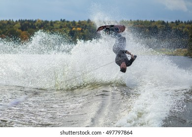 young male athlete glides on water skis on the waves on the lake