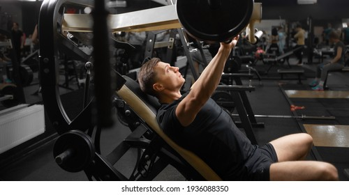 A young male athlete on the simulator in a sitting position shakes the muscles of his arms and chest. Training of muscle groups of the upper body. Trainings on simulators.
