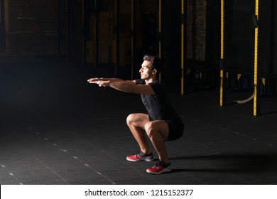 Young male athlete practicing air squats at the gym. Dark photography concept with copy space text area.