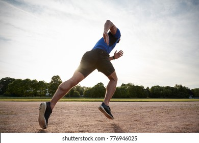 Young male athlete running at a track, low angle view