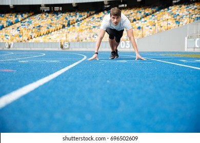 Young male athlete standing in a start position on a racetrack