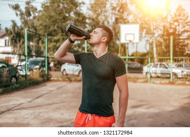 Young male athlete, in the summer on the sports field drinking water from a bottle. Active lifestyle fitness. In a t-shirt and red shorts. Absorbs thirst after a workout.