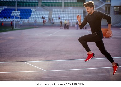 Young male athlete wearing black sportwear running at track, side view