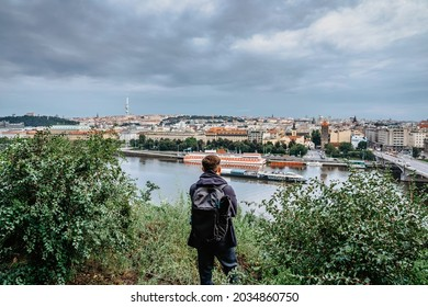 Young male backpacker enjoying view of Prague city skyline and Vltava river from Letna Park,Czech Republic.Prague panorama on cloudy rainy day.Travel urban concept.Back view of tourist man sightseeing - Shutterstock ID 2034860750