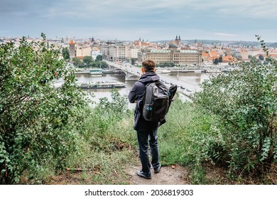 Young male backpacker enjoying view of Prague city skyline and Vltava river from Letna Park,Czech Republic.Prague panorama on cloudy rainy day.Travel urban concept.Back view of tourist man sightseeing - Shutterstock ID 2036819303