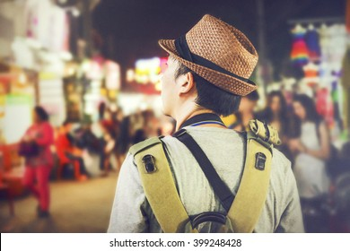 Young male backpacker walking in a famous street night market in Asia (Grainy Vintage Tone and Soft Focus)