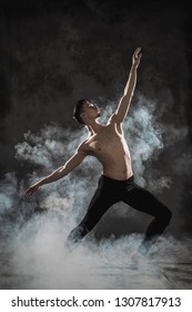 A young male ballet dancer with black leggings and a naked torso performs dance moves against a gray grunge background, with a light of lights and smoke. Conceptual art of contemporary.