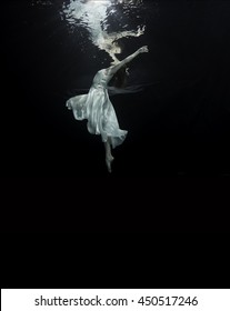 A young male ballet dancer is dancing underwater