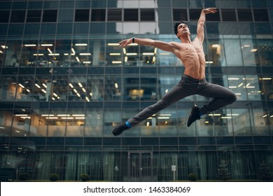 Young male ballet dancer jumping on a building background. Outdoor dance.