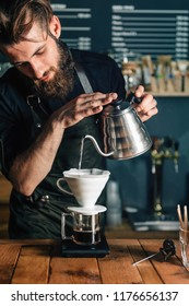 Young male barista pouring boiling water from kettle to drip coffee maker on wooden table. Barista wearing dark uniform. Tools and equipment for making Drip Brew coffee on wooden table.