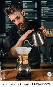 Young male barista pouring boiling water from kettle for filter coffee. Barista with  wearing dark uniform.
