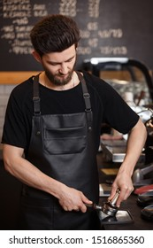 Young male barista pressing ground coffee into bottomless portafilter holder using tamper. Preparing espresso in professional coffee machine. Brewing coffee. Coffee shop concept.