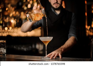 Young male bartender with black beard makes alcohol cocktail using glass with steel strainer
