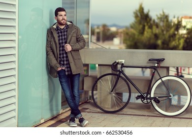 Young male beard dressed with a winter coat and blue jeans smiling.He has a vintage bicycle in the background