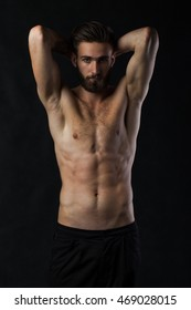 A young male with a beard is a naked body on a black background