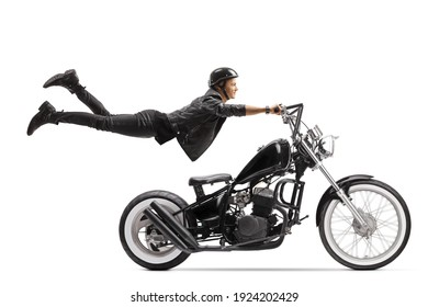 Young male biker riding a chopper and flying isolated on white background