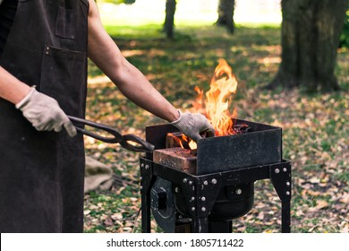 a young male blacksmith forges a product in nature, a lit hearth and a small portable hand anvil. Hammer work, metallurgy. Handmade metal. Blacksmiths Festival of craftsmanship, street exhibition.