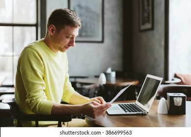 Young male blogger writes a new article to your blog while sitting at a table in the cozy bar