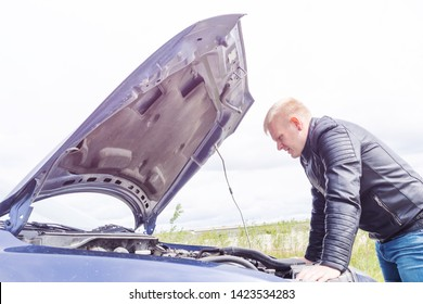 A young male blond in a leather jacket and jeans looks under the hood of the car at the engine. Trouble on the track, car breakdown. The driver is trying to fix the car.
