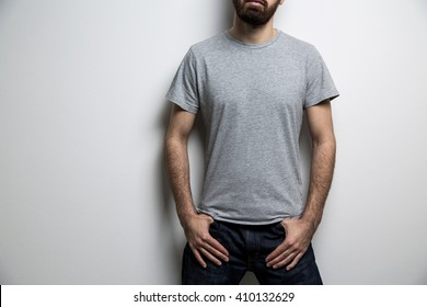 Young male body with blank grey t-shirt on light background. Mock up