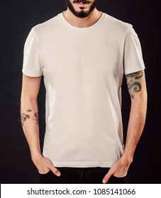 Young male body with blank white t-shirt on black background. Hipster with beard and tattoo.  Mock up
