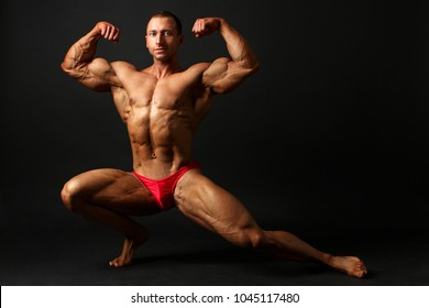 Young male bodybuilder standing knee bend, one leg squat, showing front double biceps pose. Studio photo with black background.