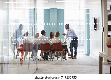 Young male boss stands leaning on table at business meeting