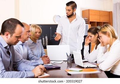 Young male boss and stressed co-workers on meeting indoors