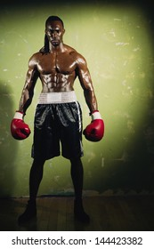 Young male boxer standing in spotlight