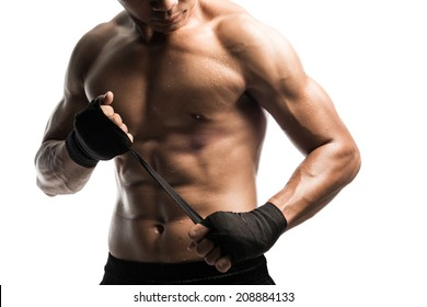 Young male boxer wrapping his hands in boxing tape before a fight.