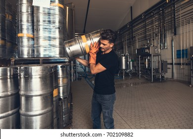 Young male brewer with keg at brewery factory warehouse. Young man working at warehouse in brewery. Arranging metal beer barrel.
