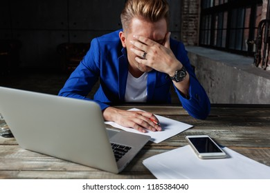 Young male businessman in blue suit, upset, tired and in depressed sitting in office at desk with laptop and phone, marketing and communication management