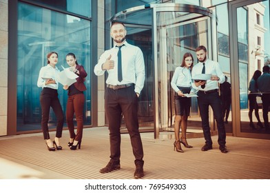 A young male businessman is enjoying a successful deal on the background of office workers. Demonstration of positive emotions and gestures. Career. Success. Shows a thumbs-up