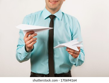 young male businessman holding origami airplanes, studio