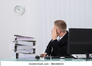 Young Male Businessman Looking At Clock In Office