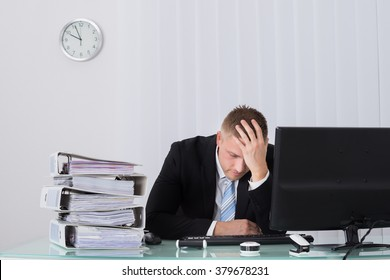 Young Male Businessman Sleeping On Desk In Office