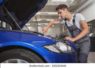 Young male car service worker repairing engine of an automobile at the garage, copy space. Auto technician working under the hood of a car